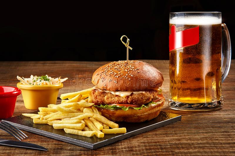 Tasty burger, french fries with sauce and glass of beer on black board royalty free stock image