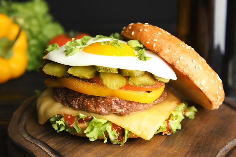Tasty burger with fried egg. On wooden board stock images