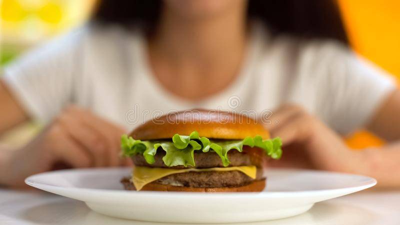 Tasty burger lying on plate, female on background, fast food restaurant, meal royalty free stock photo