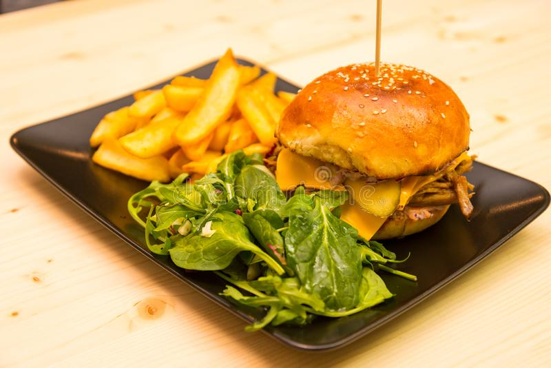 Tasty burger with salad and french fries on bistro table royalty free stock photos
