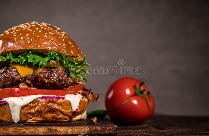 Tasty burger on wooden table. stock photography