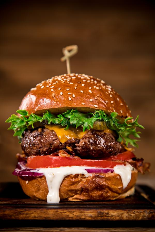 Tasty burger on wooden table. royalty free stock image