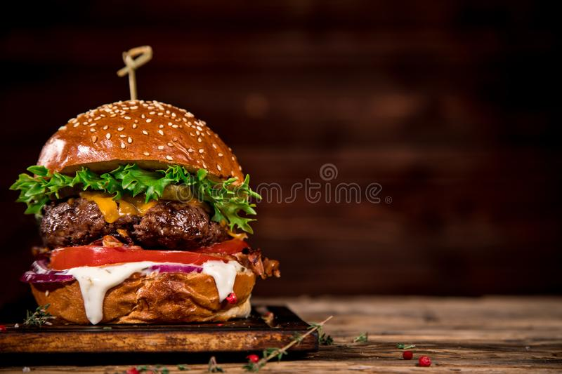 Tasty burger on wooden table. royalty free stock photography