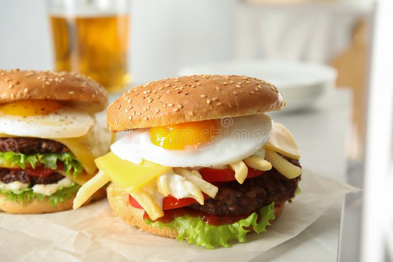 Tasty burgers with fried egg. On parchment royalty free stock images