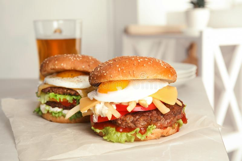 Tasty burgers with fried egg. On parchment stock images