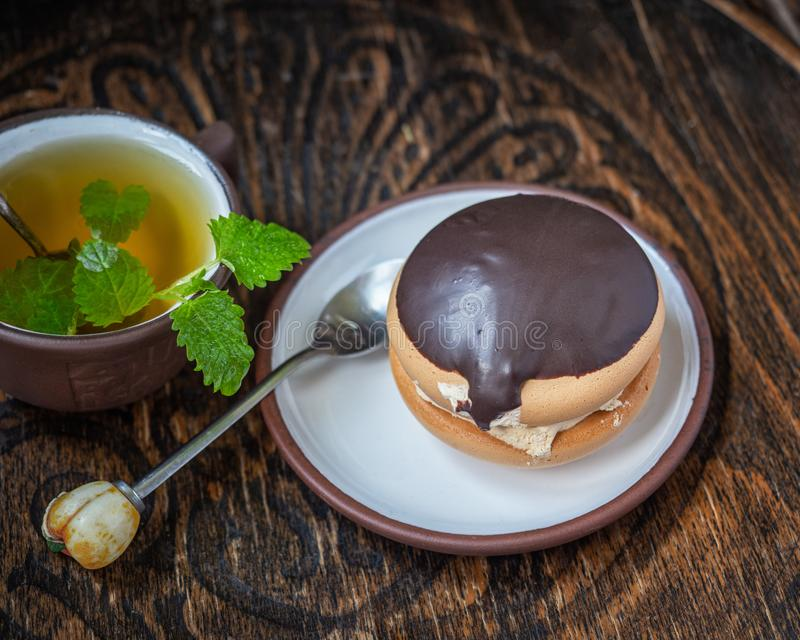 Tasty bushe cake with green tea with mint sprigs, teaspoon teaspoons on old wooden chair royalty free stock photo