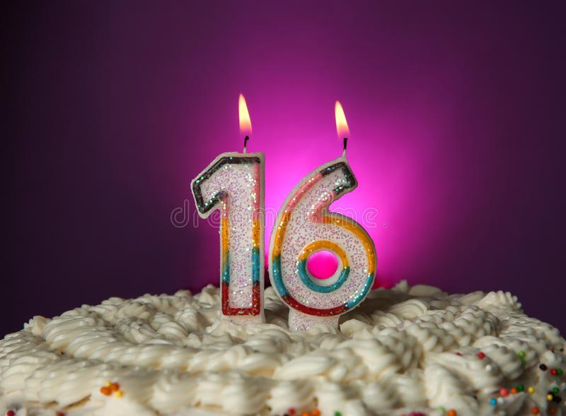 Tasty cake with candles for sixteenth birthday. On purple background royalty free stock photography