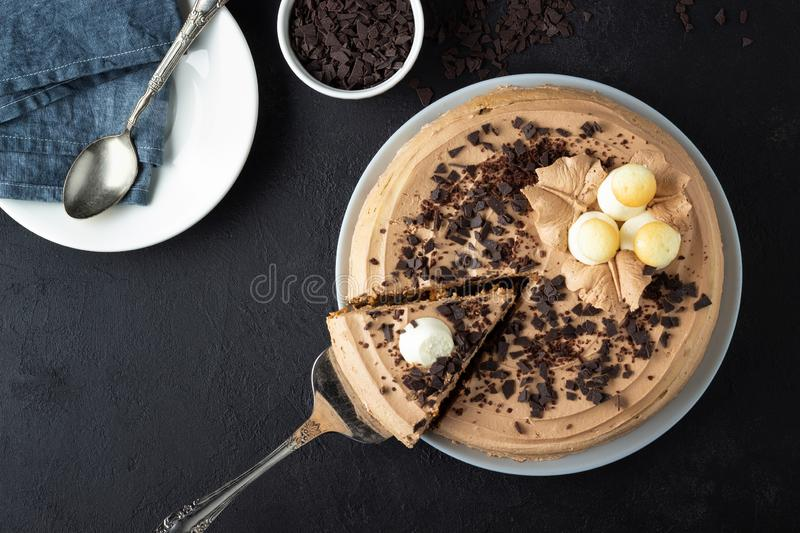 Tasty cake decorated with cream and dark chocolate on black background. Top view with copy space stock photography