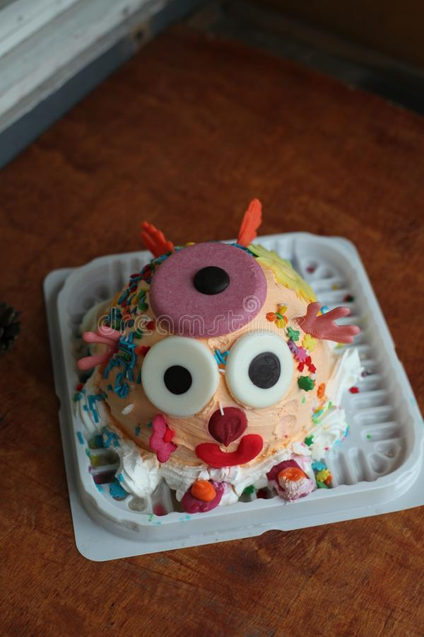 A tasty cake with a funny face made and decorated with details by the kids alone royalty free stock images