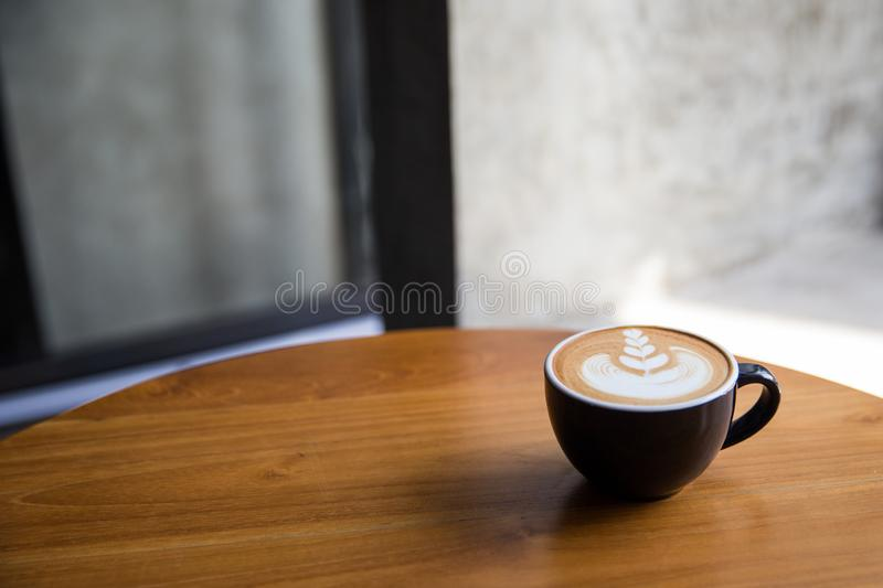 Tasty cappuccino with beautiful latte art on wooden table in the cafe. royalty free stock photo