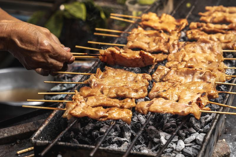 Tasty charcoal grilled pork skewer sticks sizzling on the bbq gr. Ill outdoor, moo ping, Thai street food stock images
