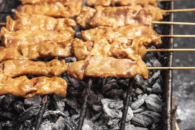 Tasty charcoal grilled pork skewer sticks sizzling on the bbq gr. Ill outdoor, moo ping, Thai street food royalty free stock photos