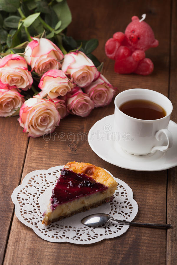 Tasty cheese cake and a cup of hot tea with roses royalty free stock image