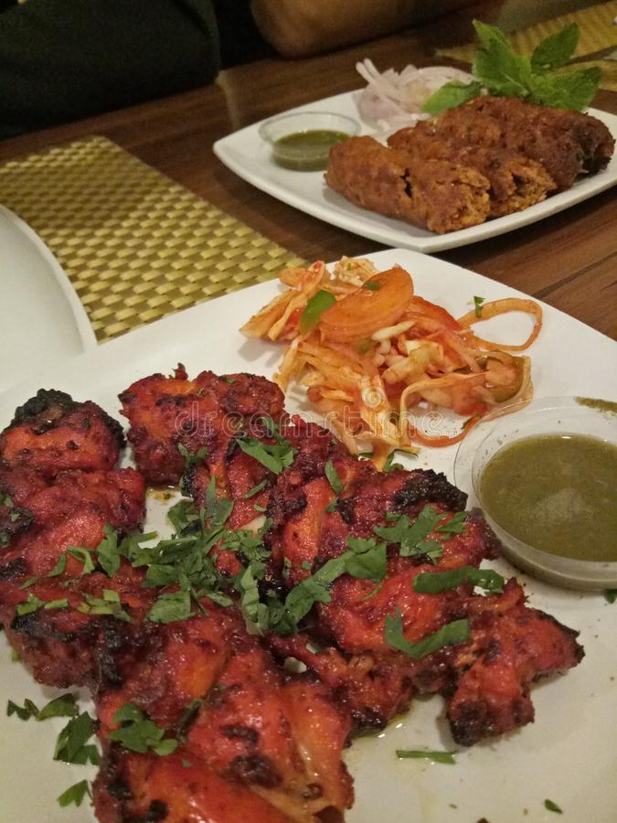 Tasty chicken tandoori. Lovely chicken tandoori and kebabs served with green chutney and salad...a finger licking dish royalty free stock photo