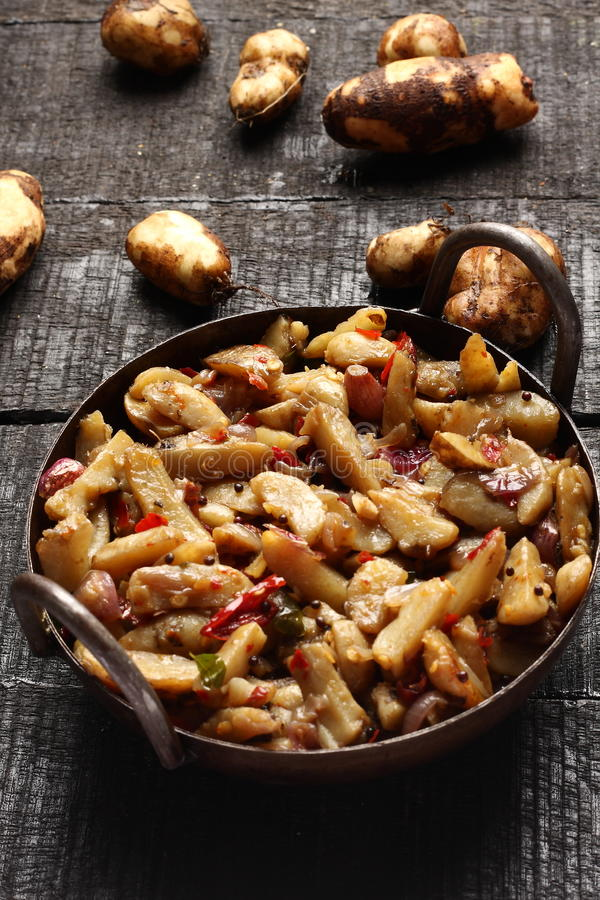 Tasty Chinese potato stir fry. Delicious Chinese potato stir fry in cast iron cookware stock photo