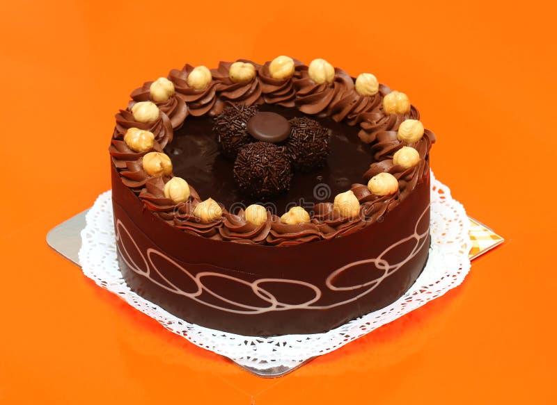 Tasty chocolate cake. Tasty dark brown chocolate cake with hazelnut decor outside royalty free stock photography
