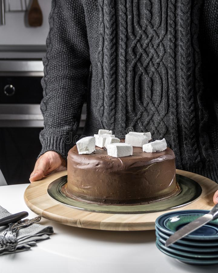 Tasty chocolate cake with marshmallow topping. Two delicious chocolate cakes with hazelnuts on the table with cups, candles, tea pot and wine corks stock photo