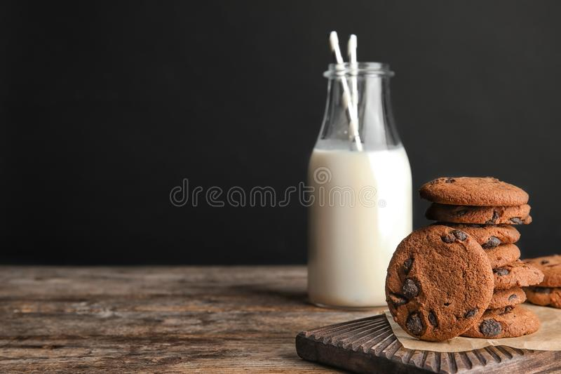 Tasty chocolate chip cookies and bottle of milk. On wooden table. Space for text stock images