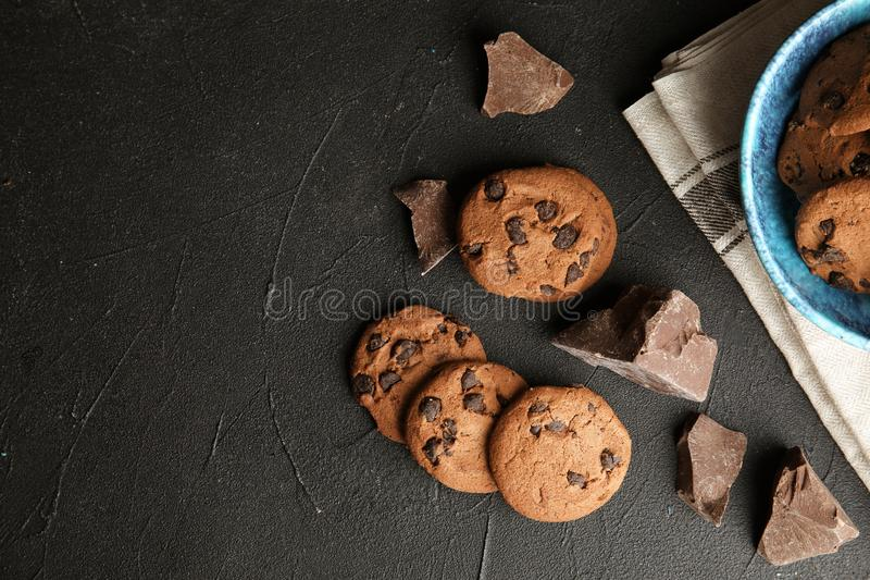 Tasty chocolate chip cookies on dark background, flat lay. Space for text stock photos