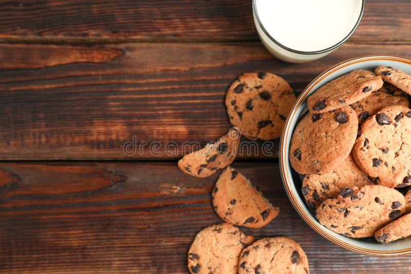 Tasty chocolate chip cookies and glass of milk on wooden table, top view stock photography