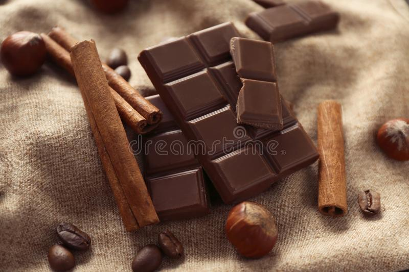 Tasty chocolate, cinnamon sticks and coffee beans on cloth royalty free stock images