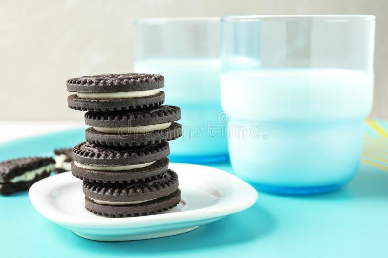 Tasty chocolate cookies with cream and milk on tray. Space for text royalty free stock photography