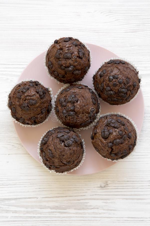 Tasty chocolate muffins on pink plate on white wooden table, top view. Overhead stock image