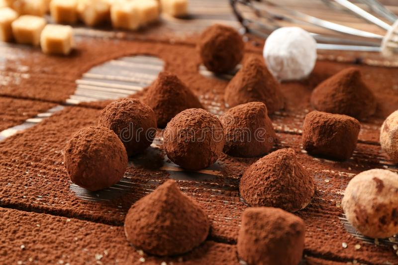 Tasty chocolate truffles powdered with cacao on table stock photos