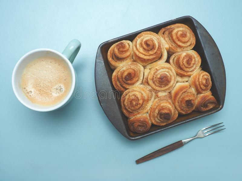 Tasty cinnamon pastry. Sweet and tasty cinnamon pastry in a ceramic baking dish, view from above, modern flat tone style royalty free stock photo