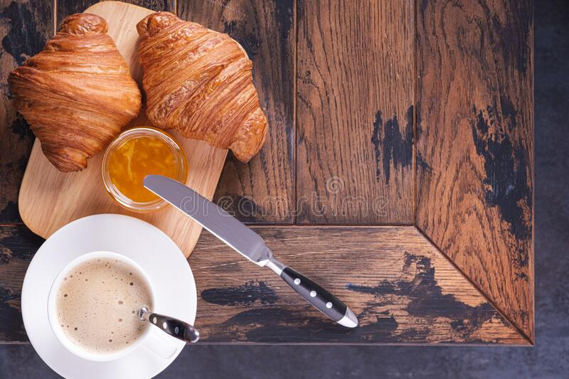 Tasty classical croissant and coffee cappuccino on table. With copy space for text stock photos