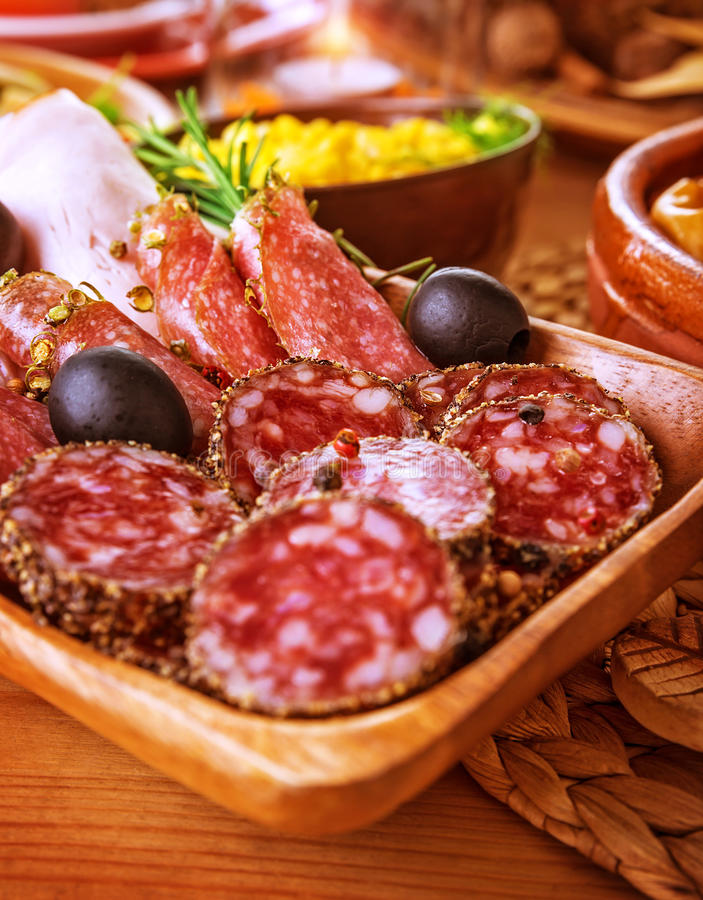 Tasty cold cuts. On wooden table at home, slices of salami, pieces of pepperoni and ham, festive menu, different kind of smoked meat stock photo