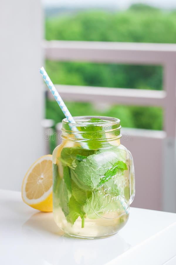 Tasty colorful drink with cold green tea, mint and lemon in a glass jar on a white kitchen background. Closeup stock photo