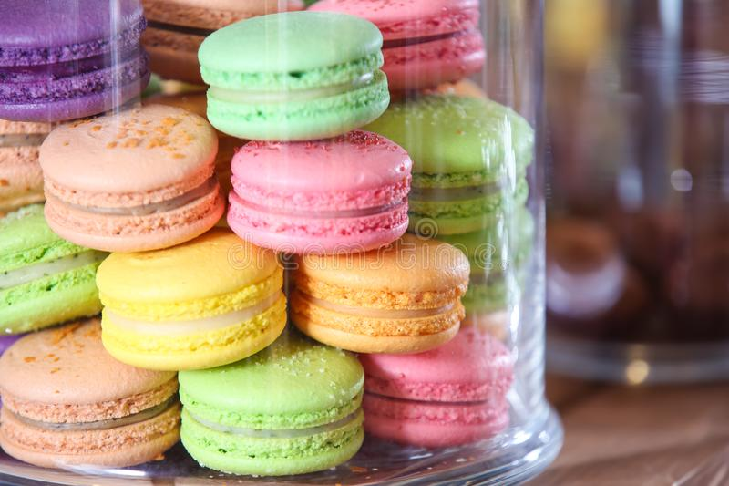 Tasty colorful macarons under glass dome stock photos