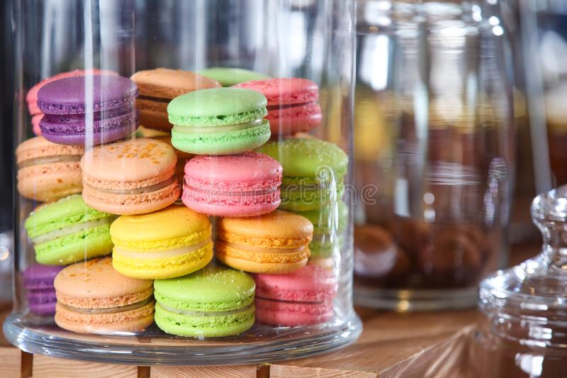 Tasty colorful macarons under glass dome on table stock photos