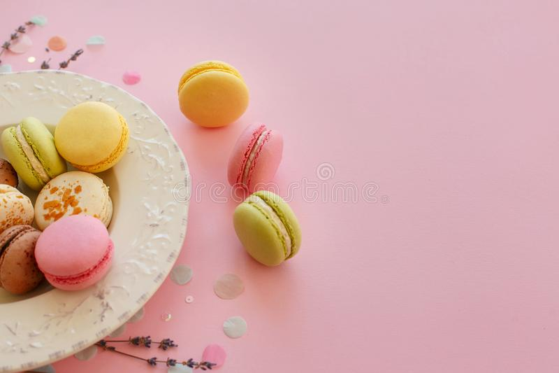 Tasty colorful macarons in vintage plate on trendy pastel pink p stock photos