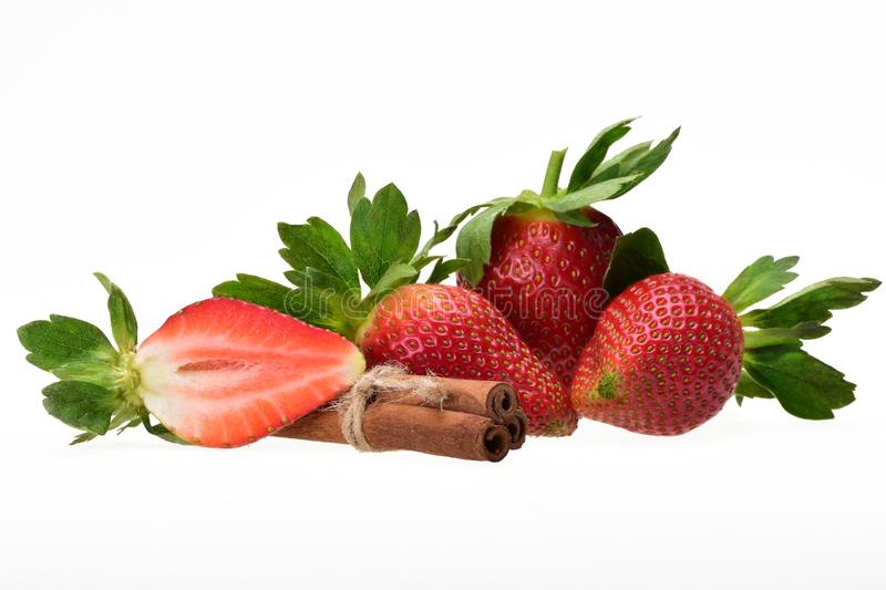 Tasty composition of ripe red strawberry berries with green petals and cinnamon sticks royalty free stock photos