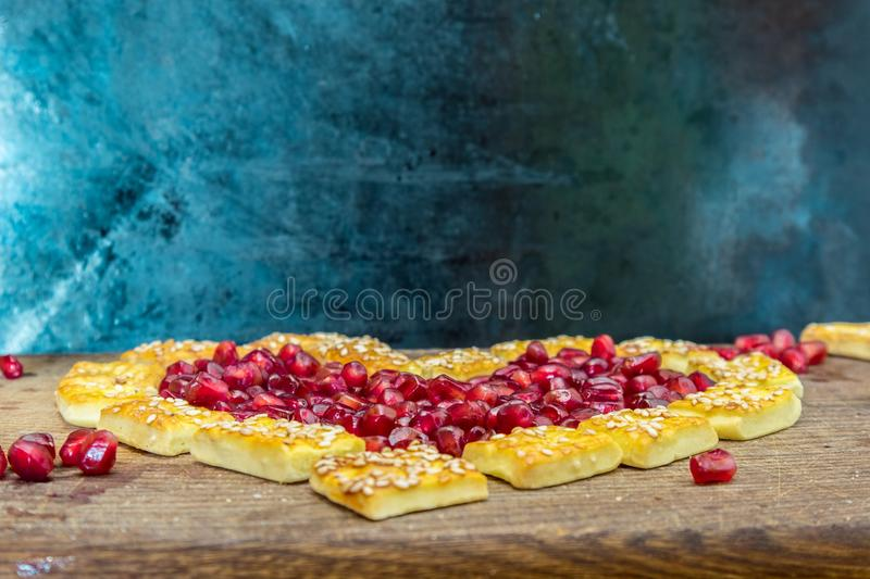Cookies and garnet hart on a cutboard royalty free stock photo