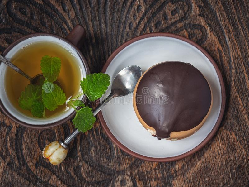 Tasty cookies with green tea with sprigs of mint, teaspoons on the old chair stock photography