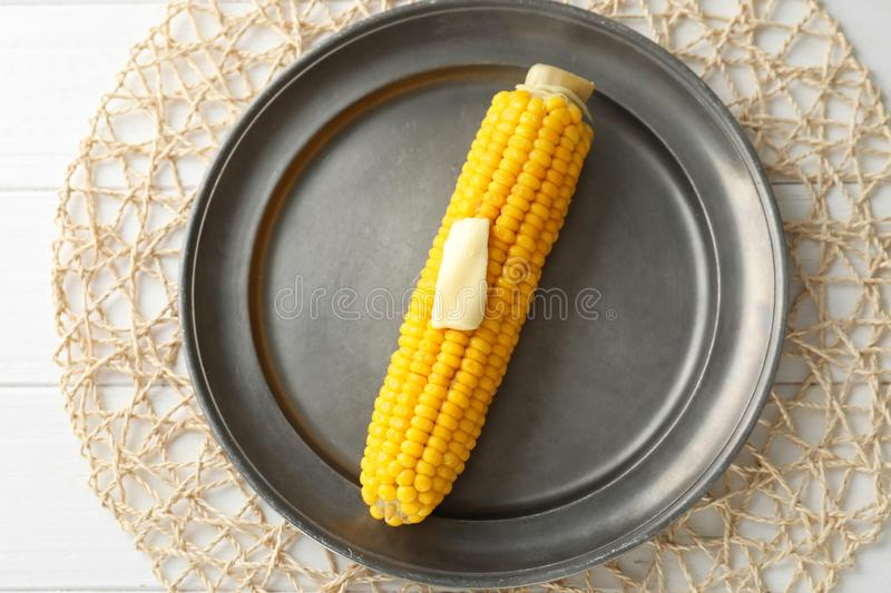 Tasty corn cob with butter on metal plate stock photos