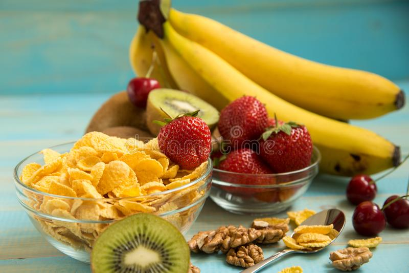 Tasty cornflakes in glass bow with walnut and strawberries,. Bananas, kiwi on blue background. Corn Flakes, Copy Spacer royalty free stock images