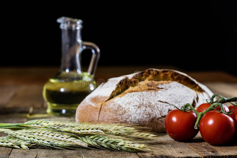 Tasty country bread and red cocktail tomatoes. Wooden table. stock photo