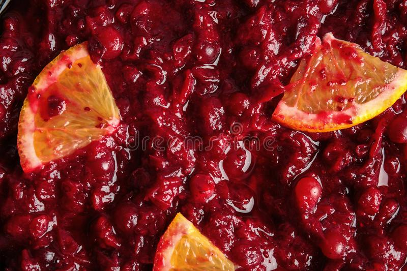 Tasty cranberry sauce with citrus fruit slices as background. Top view stock photography