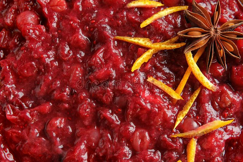 Tasty cranberry sauce with citrus zest and anise as background. Top view stock images