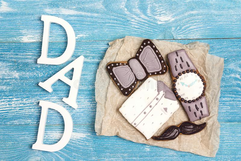Tasty creative cookies with word dad on blue wooden background. Father`s Day concept royalty free stock photos