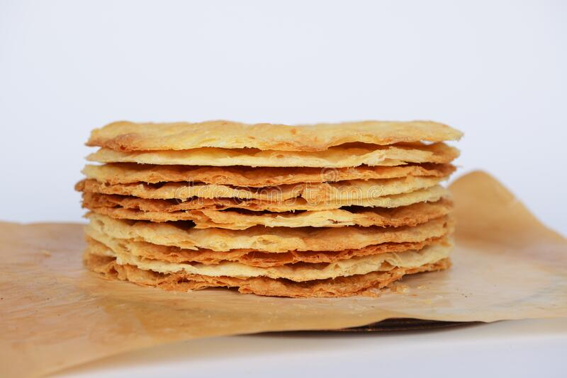 Tasty crispy baked round puff pastry layers of homemade traditional Russian napoleon cake on parchment. On white background stock image