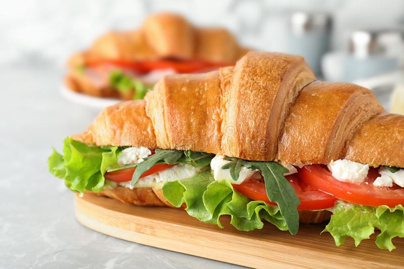 Tasty croissant sandwich with feta cheese and tomato on light grey marble table, closeup royalty free stock images