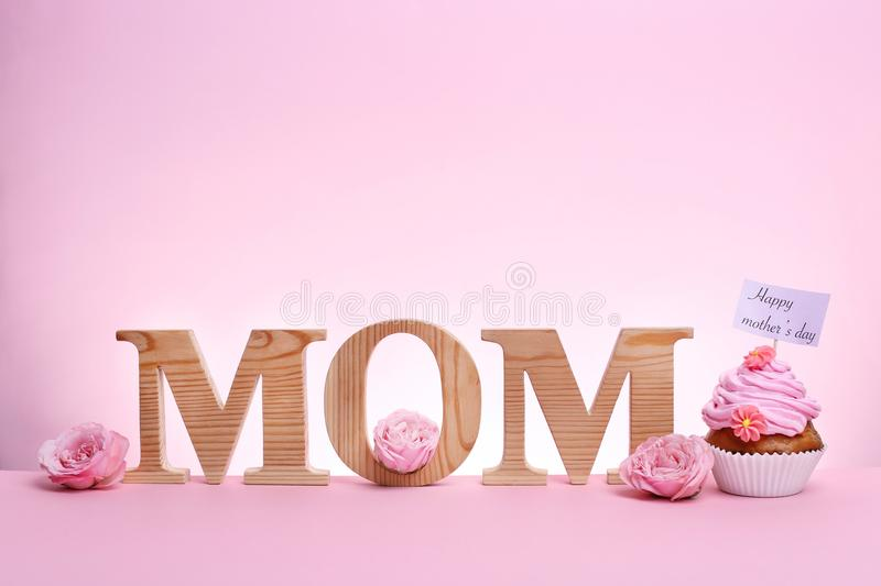 Tasty cupcake for Mother`s Day and word MOM royalty free stock photography