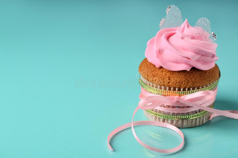 Tasty cupcake with pink ribbon on color background. Mother's Day celebration stock image