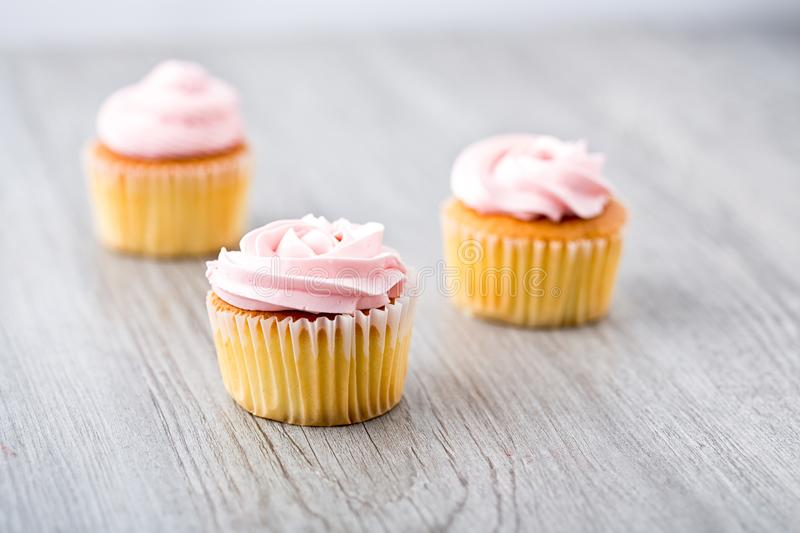 Tasty cupcake on wooden background. Birthday cupcakes on gray wooden background. Space for Text. Selective focus.  royalty free stock image