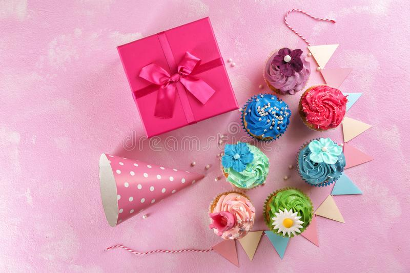 Tasty cupcakes, birthday gift and party hat on color background royalty free stock photo